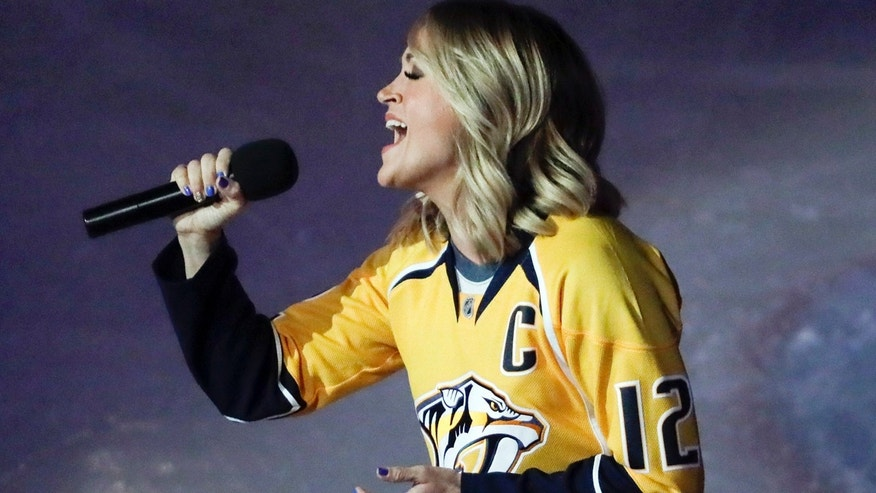 Country music star Carrie Underwood performs the national anthem before Game 3 of a first-round NHL hockey playoff series between the Predators and the Chicago Blackhawks Monday, April 17, 2017, in Nashville, Tenn. Underwood is the wife of Predators center Mike Fisher. (AP Photo/Mark Humphrey)