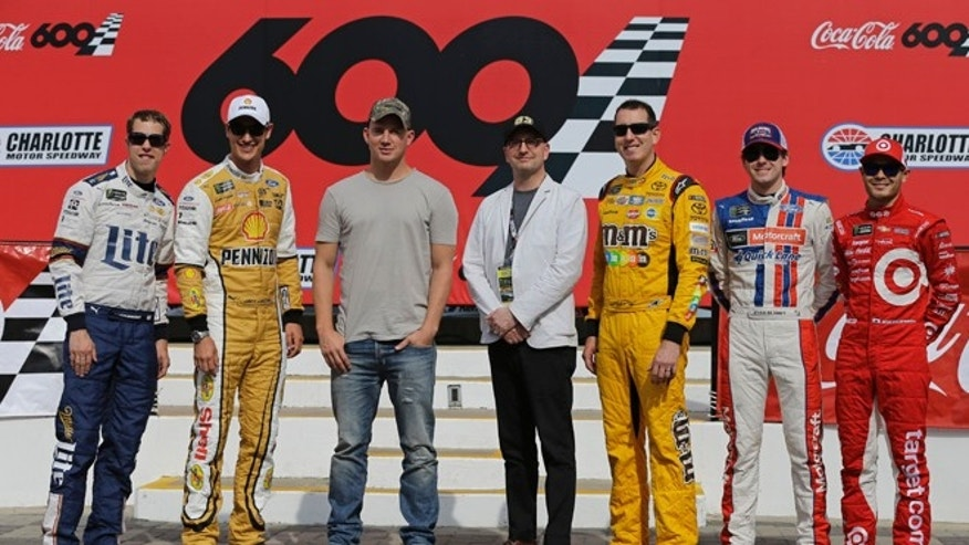 Channing Tatum, third from left, and director Steven Soderbergh, center, pose with NASCAR drivers from left, Brad Keselowski, Joey Logano, Kyle Busch, Ryan Blaney and Kyle Larson before the NASCAR Cup in Cocord, N.C.