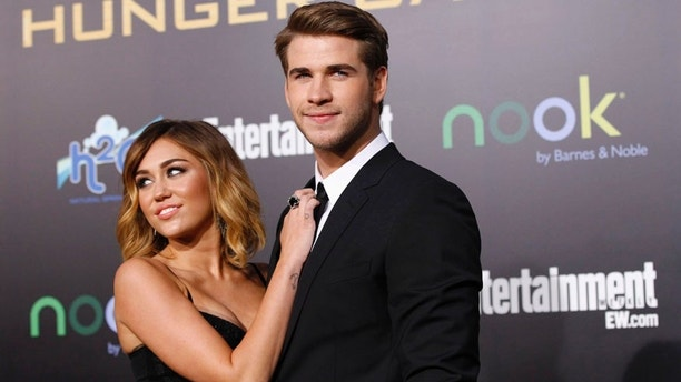 """Cast member Liam Hemsworth poses with actress Miley Cyrus at the premiere of """"The Hunger Games"""" at Nokia theatre in Los Angeles, California March 12, 2012. The movie opens in the U.S. on March 23. REUTERS/Mario Anzuoni (UNITED STATES - Tags: ENTERTAINMENT) - RTR2Z9GW"""