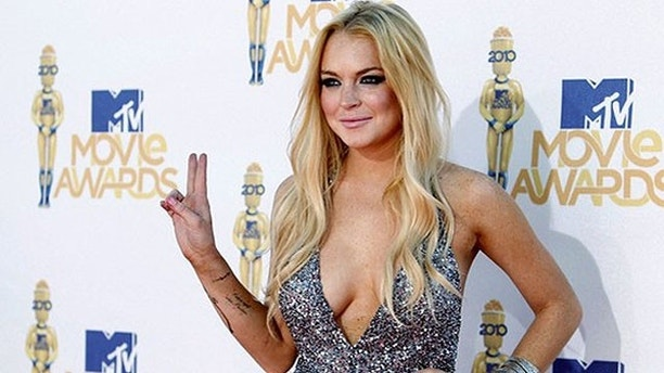 Actress Lindsay Lohan arrives at the 2010 MTV Movie Awards in Los Angeles, in this file photo taken June 6, 2010. A judge on Tuesday issued a new arrest warrant for Lohan that was quickly revoked in a fast-changing set of events after the troubled acress's court-ordered alcohol bracelet detected she had been drinking. Picture taken June 6, 2010.  REUTERS/Danny Moloshok/Files   (UNITED STATES - Tags: ENTERTAINMENT CRIME LAW)