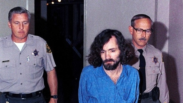 "FILE – In this Aug. 20, 1970, file photo, Charles Manson, head of the cultic ""Manson Family"" charged with murder-conspiracy in the Tate-LaBianca slayings, is escorted by deputy sheriffs to court in Los Angeles. The AP reported Friday, June 23, 2017, that stories claiming Manson is dead or free on parole are false, with California corrections officials verifying Manson remains incarcerated. (AP Photo/File)"