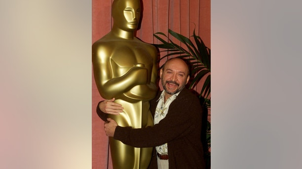 "Director Frank Darabont puts his arms around a large Oscar statue as he arrives for the Academy of Motion Picture Arts & Sciences Oscar nominee luncheon, March 13 in Beverly Hills. Darabont is nominated as best director for his film ""The Green Mile."" The Academy Awards will be presented March 26 in Los Angeles.