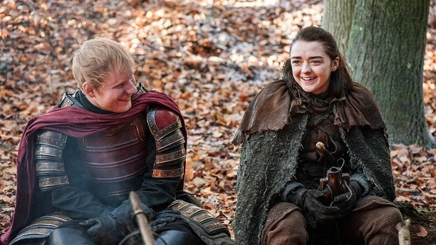 "This image released by HBO shows Ed Sheeran, left, and Maisie Williams in a scene from ""Game of Thrones."" Sheeran appeared as a Lannister soldier leading a group in song in the season premiere of the hit HBO fantasy drama, which debuted on the premium cable channel Sunday night. (Helen Sloan/HBO via AP)"