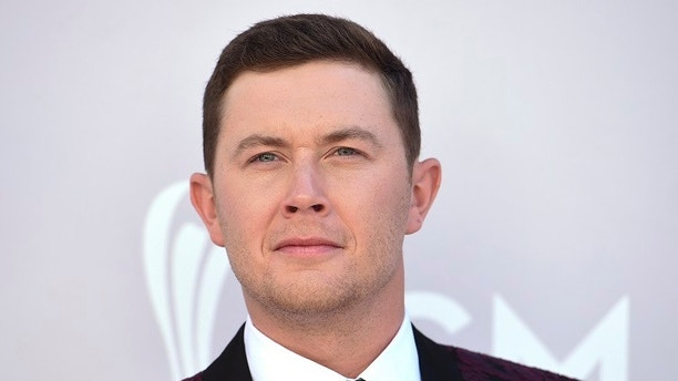 FILE - In this April 2, 2017 file photo Scotty McCreery arrives at the 52nd annual Academy of Country Music Awards at the T-Mobile Arena in Las Vegas. McCreery has been cited after authorities say he had a loaded handgun with him in Raleigh-Durham International Airport. Authorities told local media organizations that they found a loaded 9 millimeter handgun in McCreery's backpack at a security checkpoint on July 13. He told authorities he had been at a firing range and forgot to take the gun out.  (Photo by Jordan Strauss/Invision/AP, File)