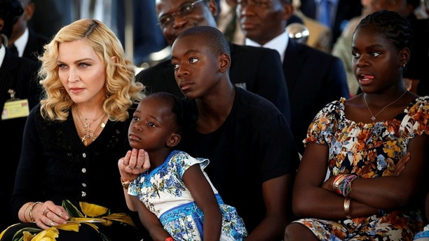 U.S singer Madonna looks on next to her children during the opening of the Mercy James hospital, in Blantyre, Malawi July 11, 2017. Picture taken July 11, 2017. REUTERS/Siphiwe Sibeko - RTX3B69M
