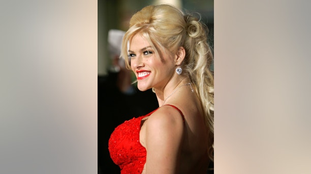 """Model Anna Nicole Smith poses as she arrives as a guest at the world premiere of the film """"Be Cool"""" in Hollywood, California February 14, 2005. The film stars John Travolta, who stars as Chili Palmer in the sequel to the original comedy """"Get Shorty"""". REUTERS/Robert Galbraith  RG/AT - RTRNCI0"""