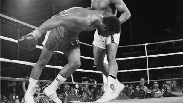 "FILE - In this Oct. 30, 1974 file photo, Challenger Muhammad Ali watches as defending world champion George Foreman goes down to the canvas in the eighth round of their WBA/WBC championship match in Kinshasa, Zaire, on Oct. 30, 1974. Foreman was counted out by the referee and Ali regained the world heavyweight crown by knockout in the bout dubbed ""Rumble in the Jungle."" (AP Photo/File)"