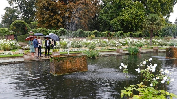 Britain's Prince William, third left, his wife Kate, Duchess of Cambridge and Prince Harry, second right, attend an event at the memorial garden in Kensington Palace, London, Wednesday, Aug. 30, 2017. Princes William and Harry are paying tribute to their mother, Princess Diana, on the eve of the 20th anniversary of her death by visiting the Sunken Garden to honor Diana's work with charities. (AP Photo/Kirsty Wigglesworth)