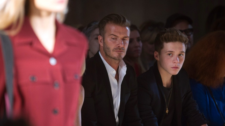 David Beckham and his son Brooklyn Beckham watch a model present a creation during the Victoria Beckham Spring/Summer 2015 collection during New York Fashion Week in the Manhattan borough of New York September 7, 2014.    REUTERS/Carlo Allegri (UNITED STATES - Tags: FASHION ENTERTAINMENT SPORT SOCCER) - RTR459GR