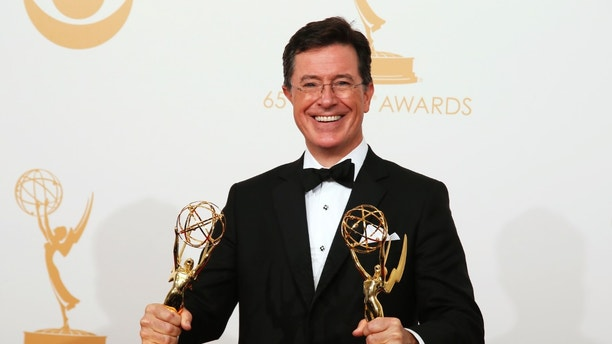 "Stephen Colbert from Comedy Centrals Variety Show ""The Colbert Report"" poses backstage with his awards for Outstanding Variety Series and Outstanding Writing For A Variety Series at the 65th Primetime Emmy Awards in Los Angeles September 22, 2013. REUTERS/Lucy Nicholson (UNITED STATES Tags: ENTERTAINMENT) (EMMYS-BACKSTAGE) - RTX13W1W"