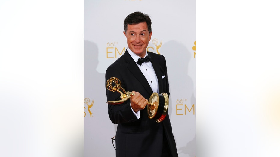 "Stephen Colbert poses with his Outstanding Variety Series award for Comedy Central's ""The Colbert Report"" at the 66th Primetime Emmy Awards in Los Angeles, California August 25, 2014. The host responded to Donald Trump's tweet about his time hosting the 2017 awards."