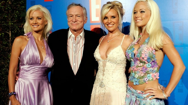Playboy founder Hugh Hefner (2nd L) and his three girlfriends Holly Madison (L), Bridget Marquardt (2nd R) and Kendra Wilkinson (R) arrive at the E! Entertainment television summer splash party at the Tropicana bar at the Roosevelt hotel in Hollywood.