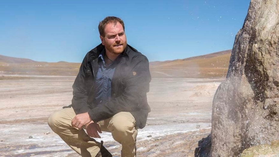 Expedition Unknown host Josh Gates stands next to one of the 80 active geysers of El Tatio Geyser field in the Chilean Andes in the Atacama desert