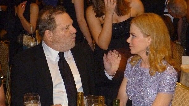 Miramax Films and Weinstein Company co-founder Harvey Weinstein (L) talks to actress Nicole Kidman (R) sits at their table at the annual White House Correspondents Association dinner as he checks his phone at the start of the dinner in Washington April 27, 2013. REUTERS/Jim Bourg (UNITED STATES - Tags: ENTERTAINMENT BUSINESS POLITICS) - GM1E94S0U1901