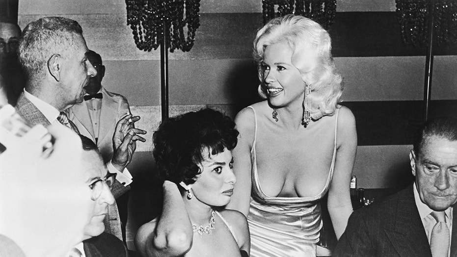 Jayne Mansfield makes an appearance at Sophia Loren's table during a promotional party for Loren, Los Angeles, California, April 12, 1957.