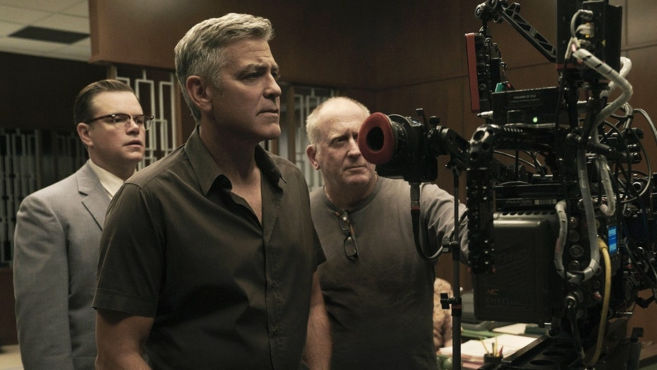 "Matt Damon, left, poses next to George Clooney, center, on the set of ""Suburbicon."""
