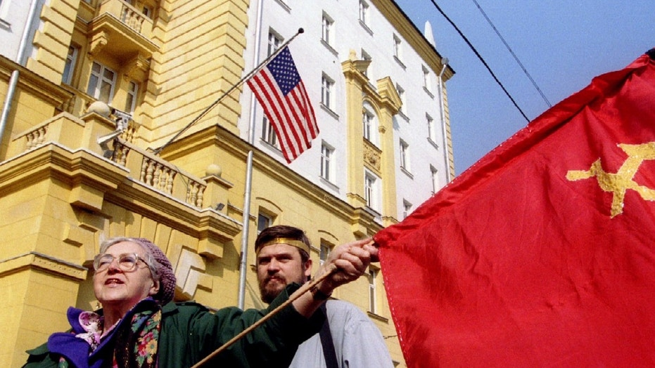 An elderly communist supporter waves the flag of the former Soviet Union in front of the US embassy during a demonstration on April 13 - PBEAHUNGLBT