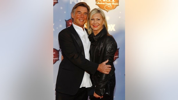 Singer Olivia Newton-John and her husband John Easterling arrive at the 4th annual American Country Awards in Las Vegas, Nevada December 10, 2013.   REUTERS/Steve Marcus (UNITED STATES  - Tags: ENTERTAINMENT)   - TB3E9CB00XSDM