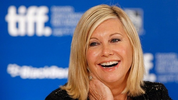 "Australian actress Olivia Newton-John smiles during the news conference for the film ""Score: A Hockey Musical"" at the 35thToronto International Film Festival September 10, 2010.   REUTERS/Mike Cassese   (CANADA - Tags: ENTERTAINMENT PROFILE) - GM1E69B04EL01"