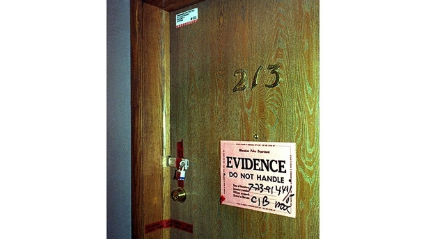 Evidence tape and a lock seals the door to the apartment on the near