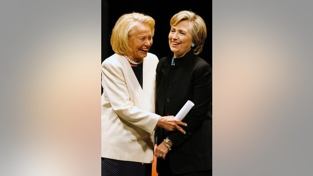 FILE- In this Sept. 18, 2006, file photo, New York gossip columnist Liz Smith, left, and Sen. Hillary Rodham Clinton, D-N.Y., share a moment after they spoke during a memorial for former Texas Gov. Ann Richards in Austin, Texas. Smith, whose mixture of banter, barbs, and bon mots about the glitterati helped her climb the A-list as high as many of the celebrities she covered, has died. Literary agent Joni Evans told The Associated Press she died in New York on Sunday, Nov. 12, 2017. She was 94. (AP Photo/Harry Cabluck, Pool, File)