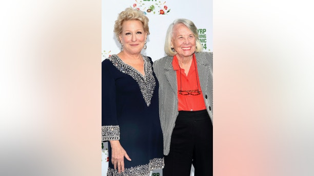 FILE- In this May 29, 2017, file photo, Bette Midler, left, and Liz Smith attend the New York Restoration Project's 13th Annual Spring Picnic at Riverside Park in New York. Smith, a gossip columnist whose mixture of banter, barbs, and bon mots about the glitterati helped her climb the A-list as high as many of the celebrities she covered, has died. Literary agent Joni Evans told The Associated Press she died in New York on Sunday, Nov. 12, 2017. She was 94. (Photo by Wendy Ploger/Invision/AP, File)