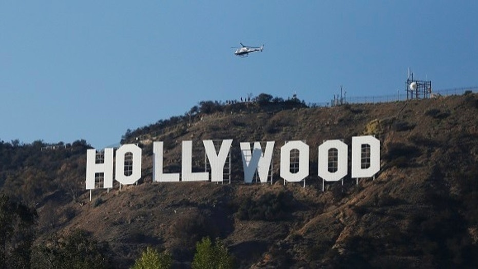 A Los Angeles Police Department helicopter flies over the Hollywood sign in Hollywood, Calif., Feb. 21, 2014.