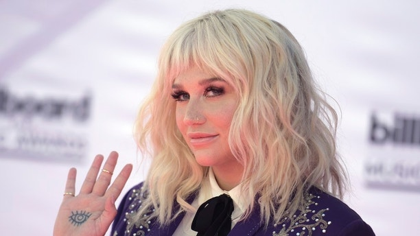 "FILE - In this May 22, 2016, file photo, Kesha arrives at the Billboard Music Awards at the T-Mobile Arena in Las Vegas. Video shows Kesha interrupting an interview Jerry Seinfeld was doing an interview with a local news reporter ahead of the ""Night of Laughter & Song"" event at the Kennedy Center Monday, June 5, 2017. The singer wanted a hug from the comedian, but Seinfeld repeatedly declined, backing off and telling her, ""no thanks."" (Photo by Richard Shotwell/Invision/AP, File)"