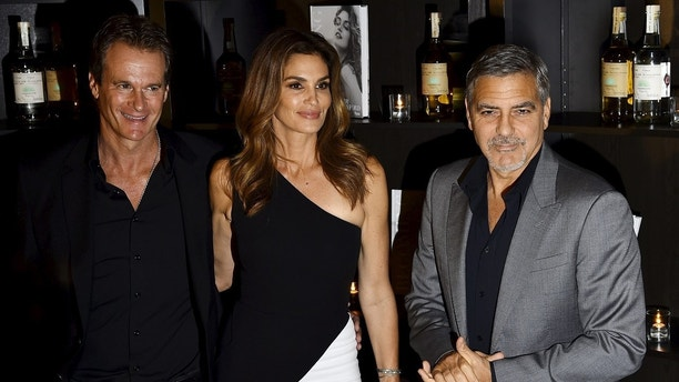 "U.S. model Cindy Crawford (C) poses with her husband and model Rande Gerber (L) and U.S. actor George Clooney (R) as she arrives for the launch party of her autobiographical book ""Becoming"" in central London, Britain, October 1, 2015. REUTERS/Toby Melville - GF10000229451"