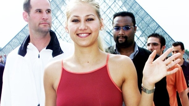 Russian tennis player Anna Kournikova (C) leaves the Louvre Pyramide after posing for photographers with her 2001 Roland Garros outfit May 24, 2001. Kournikova will not compete in the 2001 French tennis open due to a foot injury. The French open starts May 28 and will end June 10. - RTXKIGW
