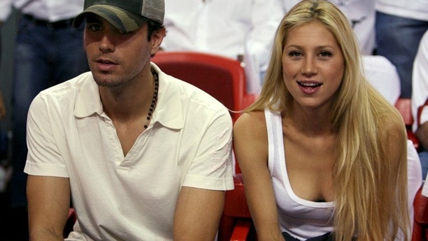 Singer Enrique Iglesias (L) and tennis star Anna Kournikova of Russia watch as the Dallas Mavericks meets the Miami Heat during Game 3 of their NBA Finals basketball game in Miami June 13, 2006.   REUTERS/Lucy Nicholson     (UNITED STATES) - RTR1EF18