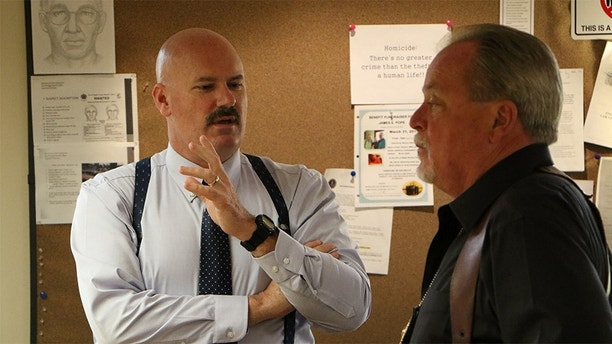 Lieutenant Thomas Potter and Investigator Randy Patrick talk in the office.