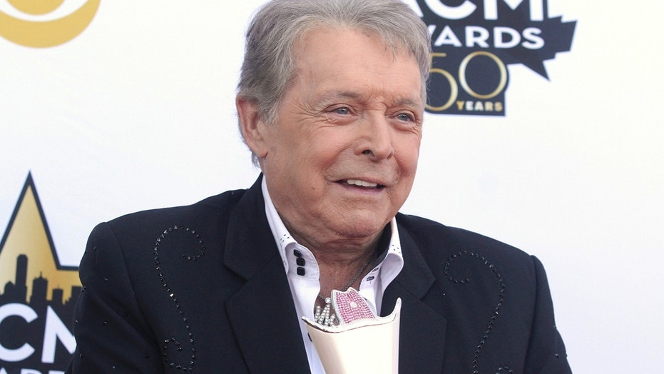 In this April 19, 2015 file photo, Mickey Gilley poses with the triple crown award on the red carpet at the 50th annual Academy of Country Music Awards at AT&T Stadium in Arlington, Texas. Country music artist Gilley and his son were injured in a car accident in Texas, but both are recovering after minor injuries. A statement from Gilley's publicist on Thursday, Jan. 4, 2018, said the two were injured Wednesday when their car rolled over.