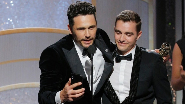"This image released by NBC shows James Franco, center, embracing his brother Dave Franco as he accepts the award for best actor in a motion picture comedy or musical for his role in ""The Disaster Artist,"" as Tommy Wiseau, left, looks on at the 75th Annual Golden Globe Awards in Beverly Hills, Calif., on Sunday, Jan. 7, 2018. (Paul Drinkwater/NBC via AP)"