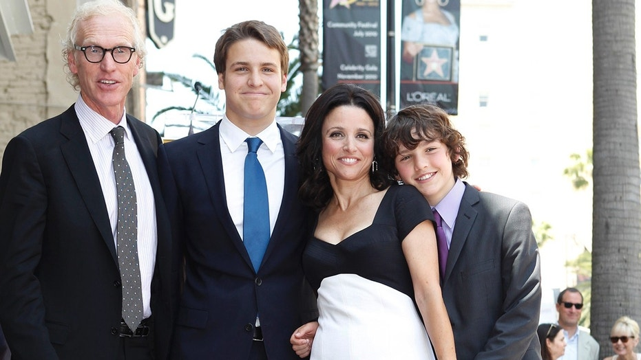 "Julia Louis-Dreyfus stands next to her star on the Hollywood Walk of Fame with husband Brad Hall (L) and sons Henry and Charlie (R) in Hollywood, California May 4, 2010. The actress, who has been battling breast cancer, posted a video in which her sons tell their mom's cancer to ""beat it"" after she completed her final chemotherapy treatment."
