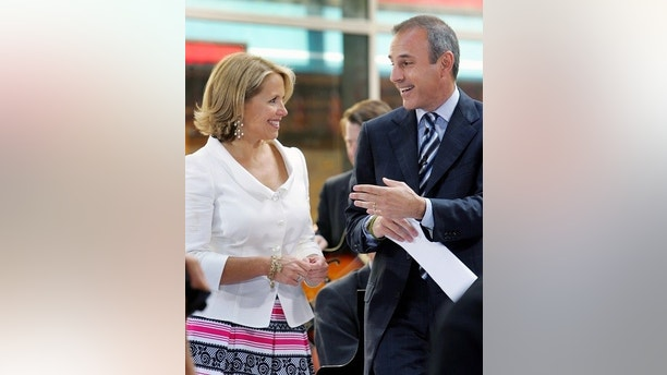 "NBC ""Today"" show host Katie Couric (L) stands with her co-host Matt Lauer in the outside portion of the ""Today"" set in New York's Rockefeller Plaza, May 31, 2006. Couric, who was appearing on her last ""Today"" show after 15 years on the program, is leaving to anchor the ""CBS Evening News"" where she will start in September.   REUTERS/Mike Segar - GM1DSSPBRQAA"