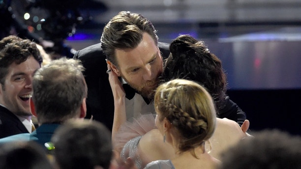 "Ewan McGregor, left, kisses Mary Elizabeth Winstead before accepting the award for best actor in a movie made for TV or limited series for ""Fargo"" at the 23rd annual Critics' Choice Awards at the Barker Hangar on Thursday, Jan. 11, 2018, in Santa Monica, Calif."