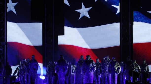 Kendrick Lamar (left, rear, in white shirt) performs a medley in front of an American flag at the 60th Annual Grammy Awards on Jan. 28, 2018.