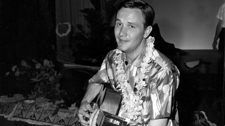 Singer-songwriter Roger Miller, 29, wears a lei and plays the guitar during taping of the Andy Williams television show in Los Angeles, Ca., in July 1965.