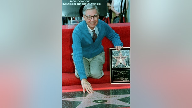 "Television personality Fred Rogers of public television's ""Mister Rogers' Neighbourhood,"" poses with a plaque he received at the ceremony to unveil his star on the Hollywood Walk of Fame, in Hollywood January 8. The popular and award winning children's program is celebrating its 30th anniversary. Rogers' is the 2,101th star on the Walk of Fame.