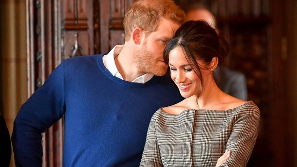 Britain's Prince Harry whispers to Meghan Markle as they watch a performance by a Welsh choir in the banqueting hall during a visit to Cardiff Castle in Cardiff, Britain, January 18, 2018.