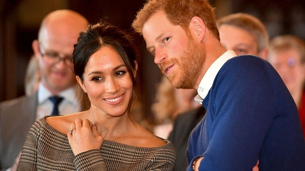Britain's Prince Harry whispers to Meghan Markle as they watch a dance performance by Jukebox Collective in the banqueting hall during a visit to Cardiff Castle in Cardiff, Britain, January 18, 2018.