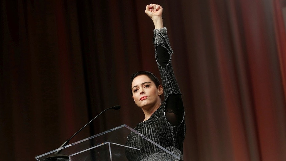 Actor Rose McGowan raises her fist after addressing the audience during the opening session of the three-day Women's Convention at Cobo Center in Detroit, Michigan, U.S., October 27, 2017.