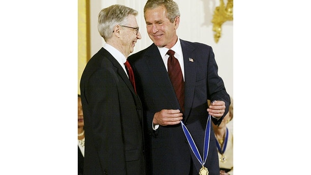 U.S. President George W. Bush laughs alongside Fred Rogers during the