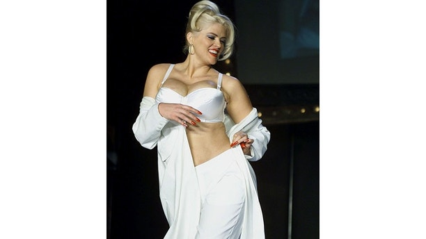 Model Anna Nicole Smith wears a long coat with pants as she walks down the runway at the Lane Bryant fashion show, February 5, 2001 in New York City.
