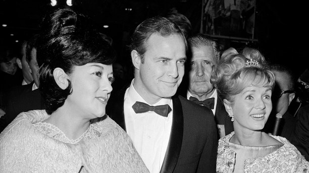 """FILE-This Nov. 15, 1962 file photo shows Marlon Brando, his wife, Mexican actress Movita Castaneda, left, and actress Debbie Reynolds, right, arriving for the West Coast premiere of """"Mutiny on the Bounty"""" at the Hollywood Egyptian Theater in Los Angeles. Castaneda, the dark-haired actress who met Brando on a movie set and later married him and had two of his children died Thursday, Feb. 12, 2015 at a Los Angeles rehabilitation center after being treated for a neck injury. The Los Angeles Times says Castaneda was believed to be 98. (AP Photo/David F. Smith,File)"""