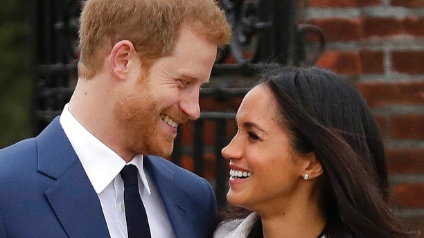 FILE - In this file photo dated  Monday Nov. 27, 2017, Britain's Prince Harry and his fiancee Meghan Markle pose for photographers in the grounds of Kensington Palace in London, following the announcement of their engagement. Prince Harry and his fiancee, American actress Meghan Markle, have released more details about their May 19 wedding, revealing that the event will include a carriage ride through Windsor so they can share the big day with the public. The couple will marry at noon in St George's Chapel, the 15th-Century church on the grounds of Windsor Castle that has long been the backdrop of choice for royal occasions. Harry's grandmother, Queen Elizabeth II, gave permission for use of the venue and will attend the wedding.  (AP Photo/Matt Dunham, File)
