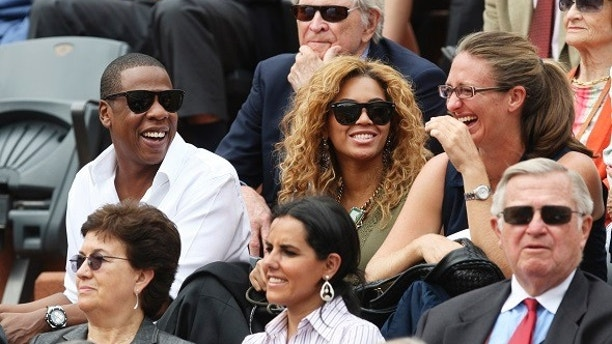 Tennis - French Open - Roland Garros, Paris, France - 6/6/10  Rapper Jay Z (L) and wife and singer Beyonce Knowles watch the action during the French Open Mens Singles Final also pictured is Mary Pierce - France  Mandatory Credit: Action Images / Paul Childs - MT1ACI7037121