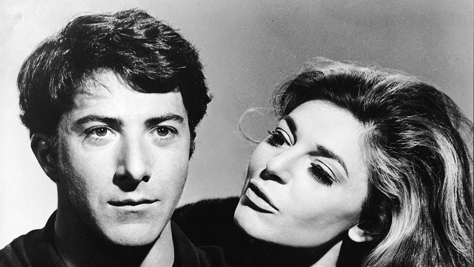 "American actress Anne Bancroft (1931 - 2005), in character as the seductive older woman Mrs. Robinson, looks at American actor Dustin Hoffman, as Benjamin Braddock, in a publicity still from the film ""The Graduate"" directed by Mike Nichols, California, 1967."