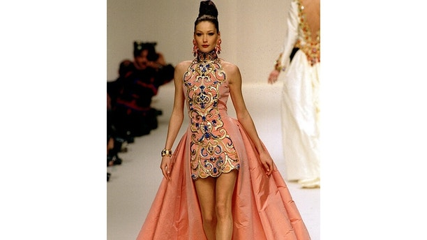 Fashion model Carla Bruni wears this short taffeta evening dress with arabesque embroidery and long back skirts as part of Danish designer Erik Mortensen' 1994 Spring-Summer haute couture collection for Jean-Louis-Scherrer, January 17 - PBEAHUNFUCN